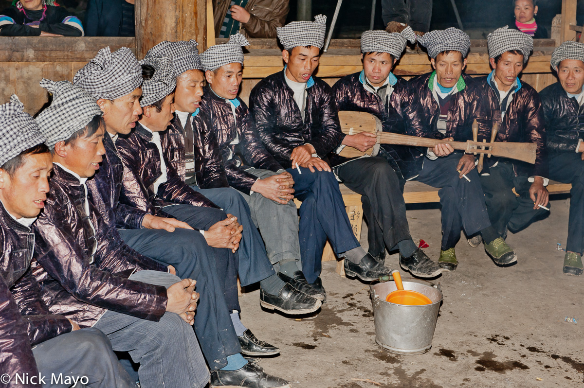 A male Da Ge ensemble singing at a Dong festival in Xiaohuang accompanied by a stringed instrument .