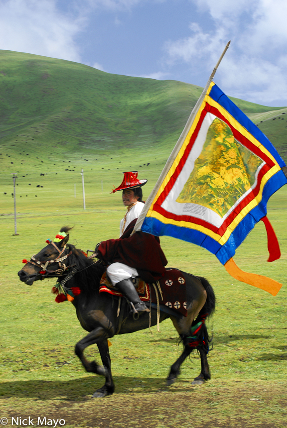 A Tibetan horsemen carrying a standard at the opening day of a Sershul horse festival.