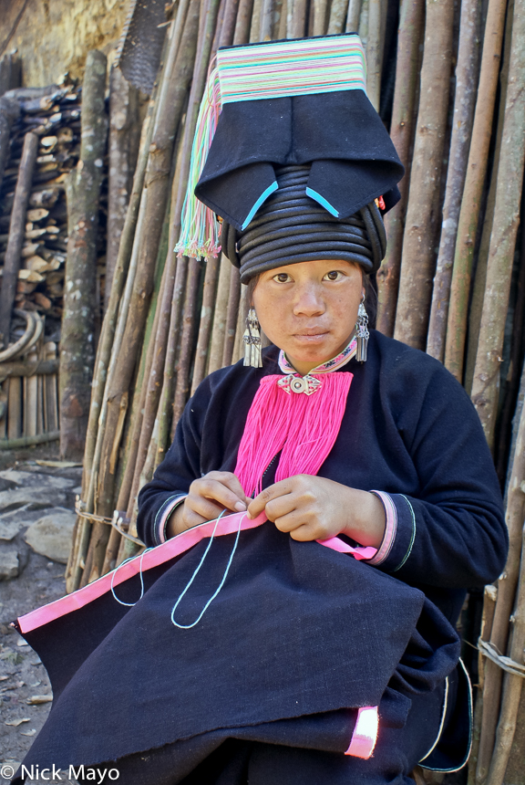 A Pintoh Yao girl wearing a traditional flat topped hat stitching in Nan Ke village.