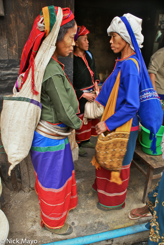 Two Golden Palaung women at Namshan wearing waist hoops and carrying their bags by head straps.