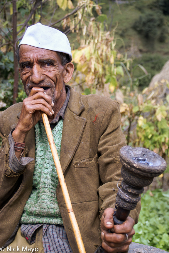 A man smoking his long stemmed pipe in Kema village in the Ram Ganga valley.
