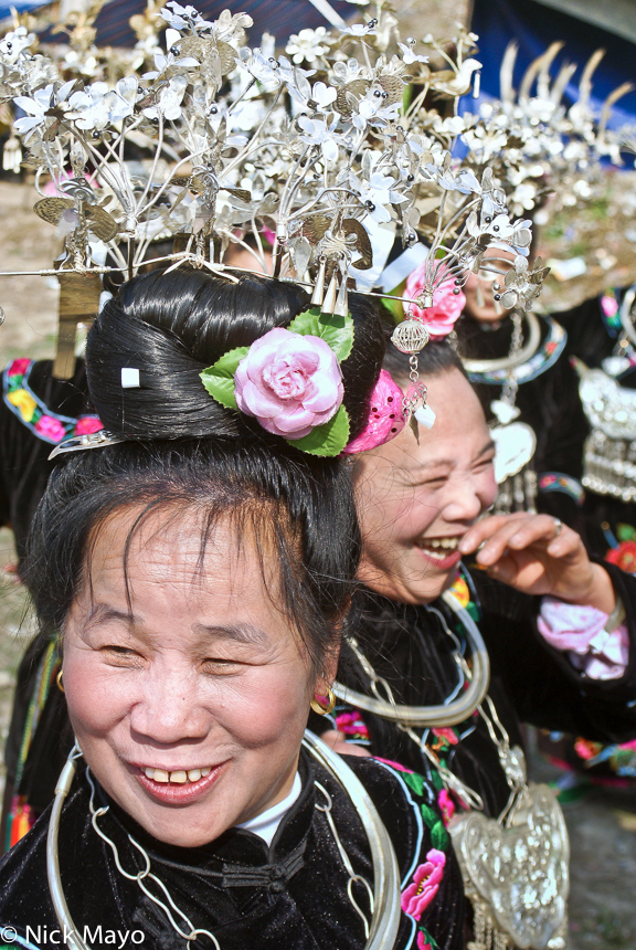 Miao woman wearing ornate silver hairpieces and heavy necklaces at a festival in Zhouxi.