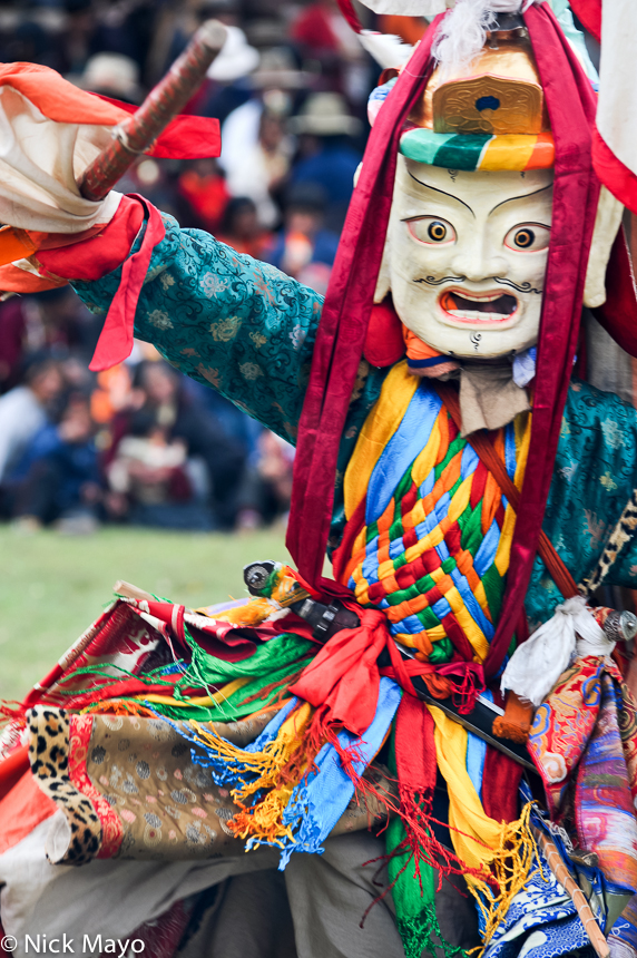 A masked Tibetan monk dancing at a festival at the Yazer Gon monastery in Manigango.