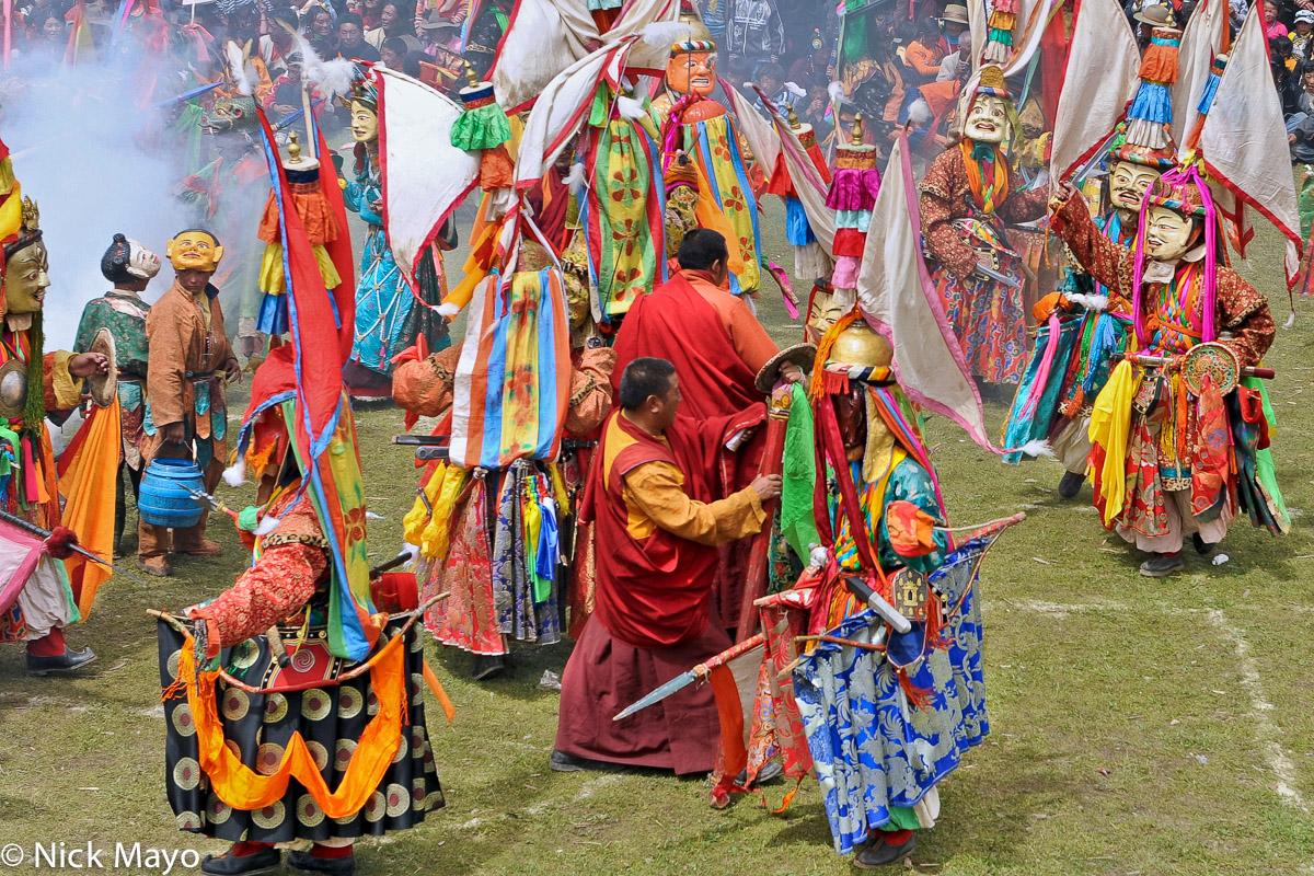 Masked monks wearing spectacular hats and carrying swords participating in the final dance at a festival at the Tibetan monastery...