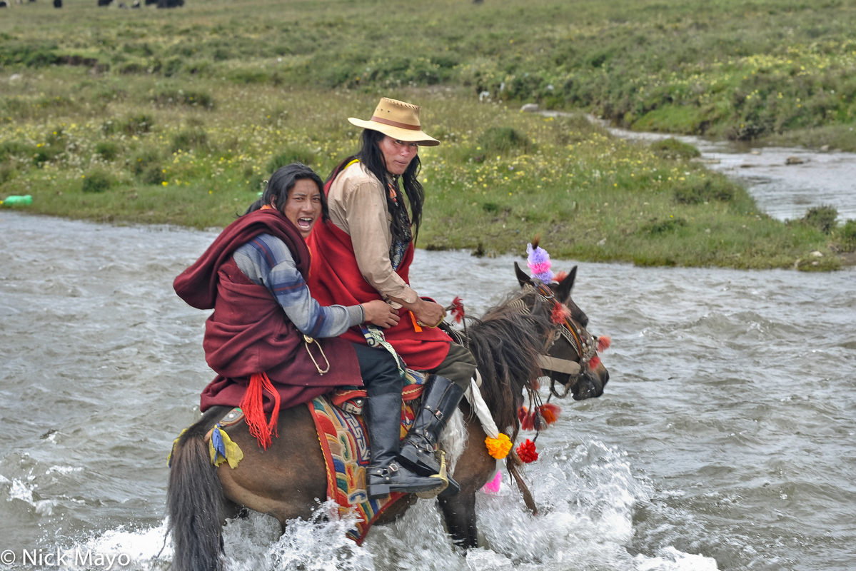 A Khampa Tibetan man crossing a river by horse with his partner during a festival at Sershul.
