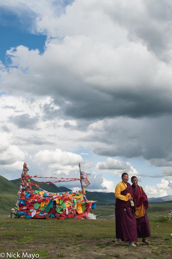 Two Tibetan nuns on an afternoon walk near hillside prayer flags at Yaqing.