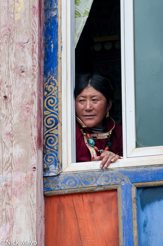 A Tibetan woman peering from a window during a festival at Manigango.