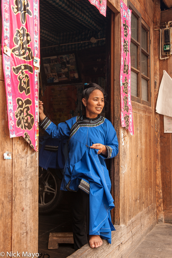 A woman standing in a doorway in the Dong village of Da Li.