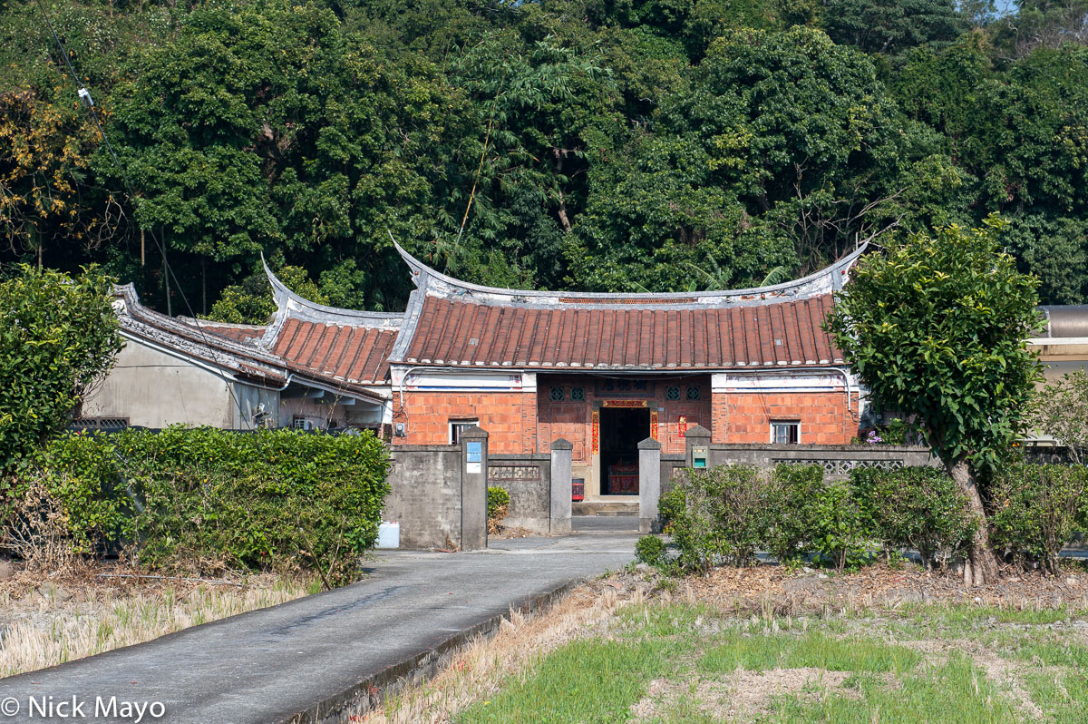 A traditional farmhouse with a swallow tail roof near Xinpu.