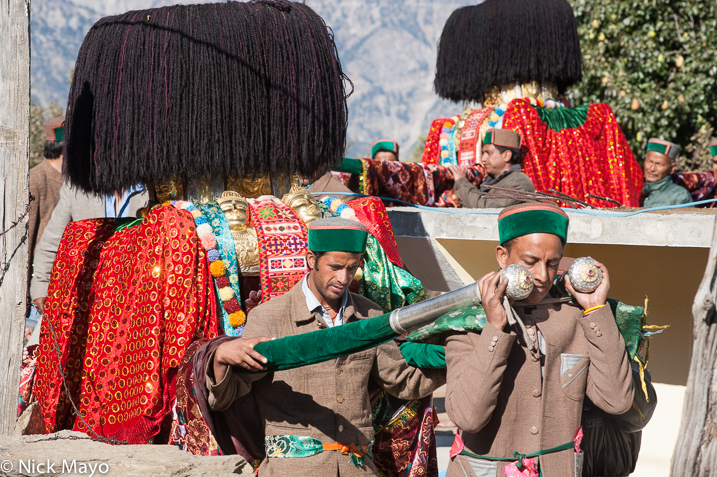 Two Kinnaur men wearing traditional green hats carrying a palanquin at a festival in Kalpa.