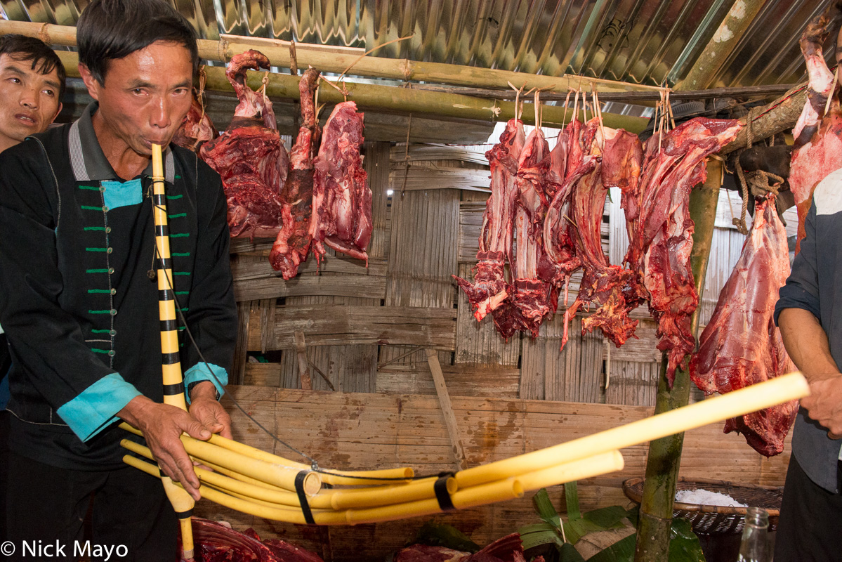 A piper playing ritual music to appease the spirits of animals killed for their meat at a festival in the White Hmong village...