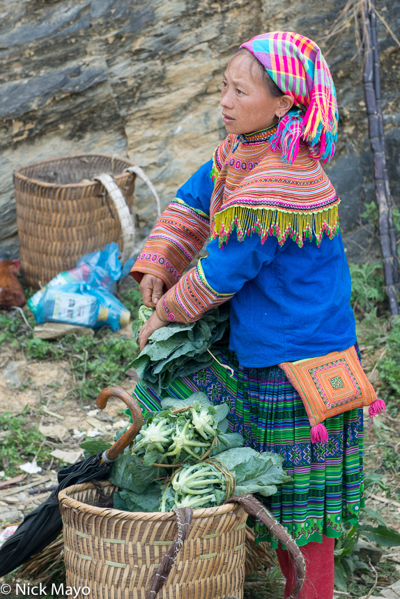 A Hmong woman, wearing a pleated skirt and checked headscarf, with a basket of vegetables at Si Ma Cai market.