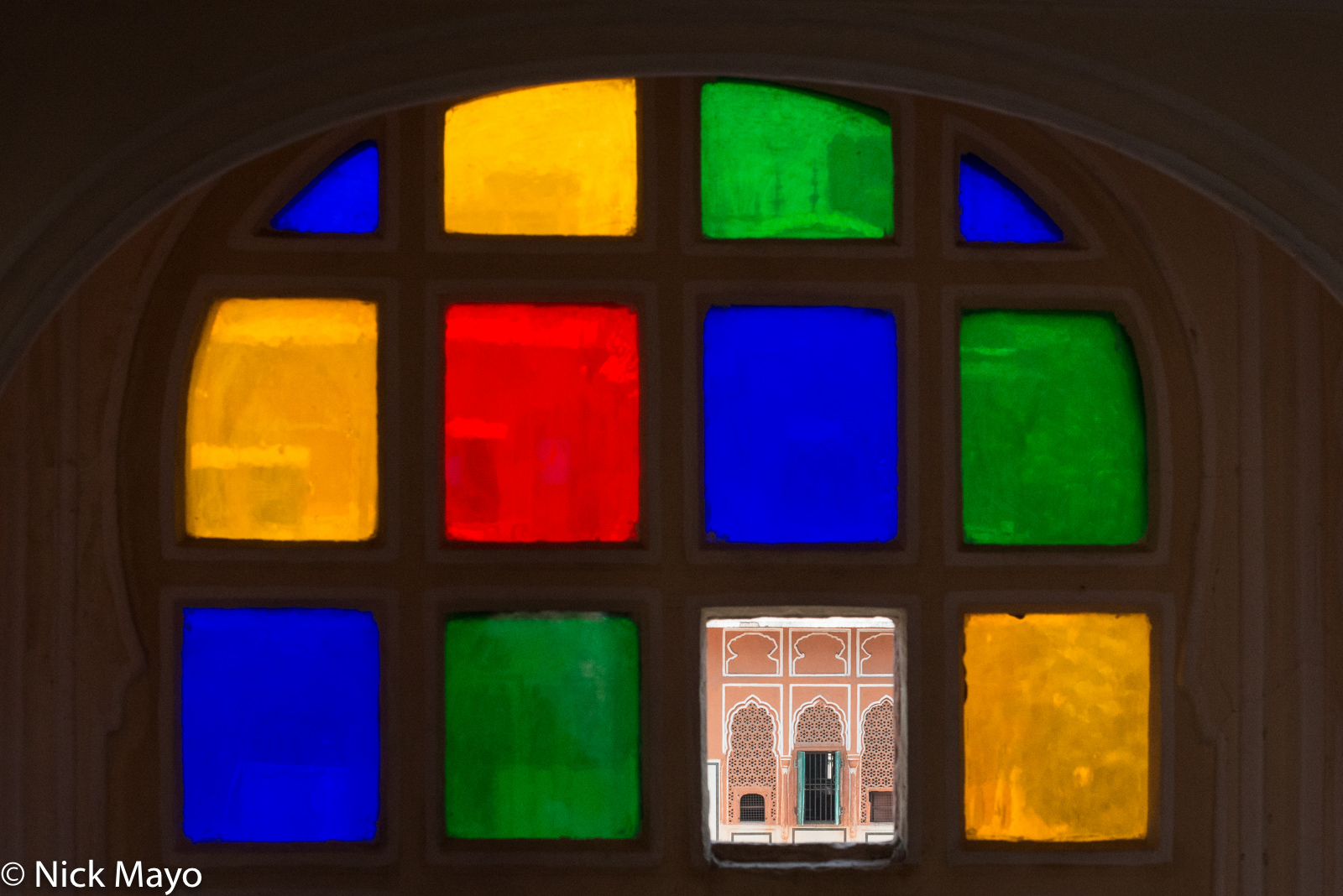 A view through a broken pane of a stained glass window at the Hawa Mahal in Jaipur.