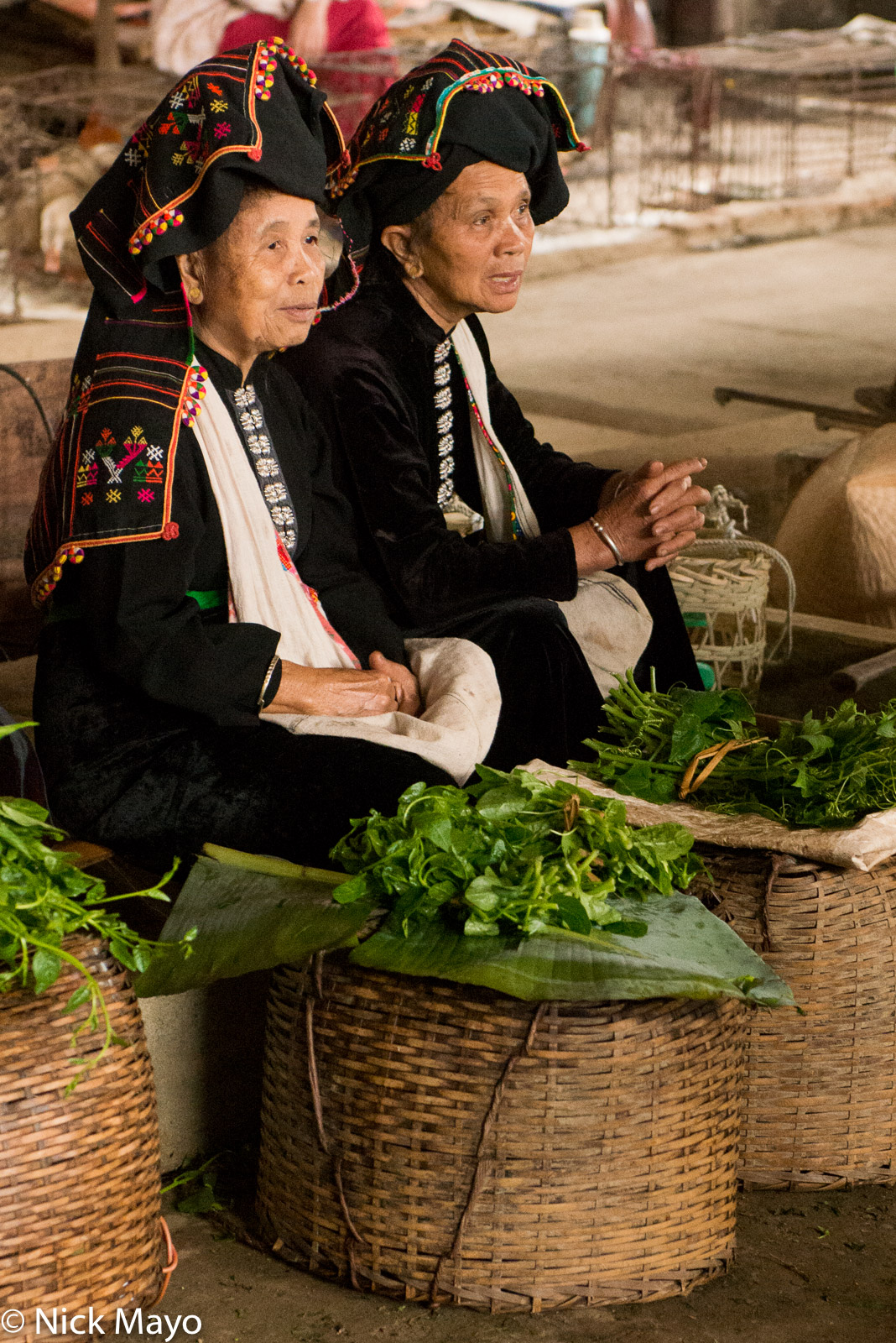 Two Black Thai women selling vegetables at Thuan Chau market.