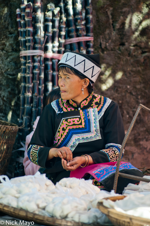 A Hani lady, in traditional clothes and hat, selling soy at Pinghe market.