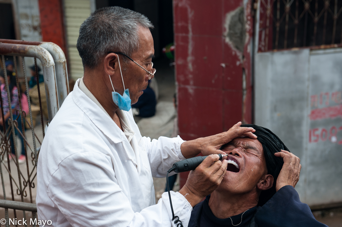 A Han dentist at work on a Yi patient at the Yi market of Tuo Mu Guo in Daliangshan.