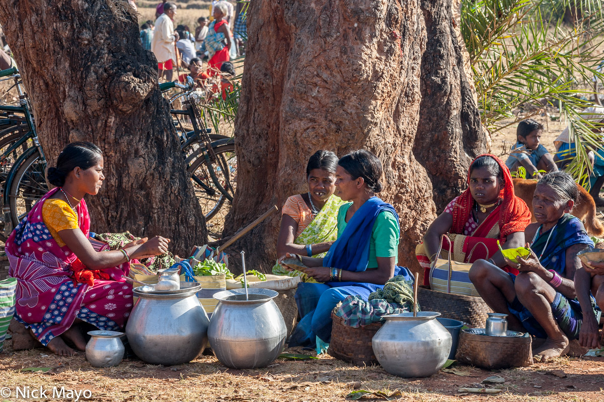 Maria women of the Gond ethnicity selling mahuli from containers at Madum market.