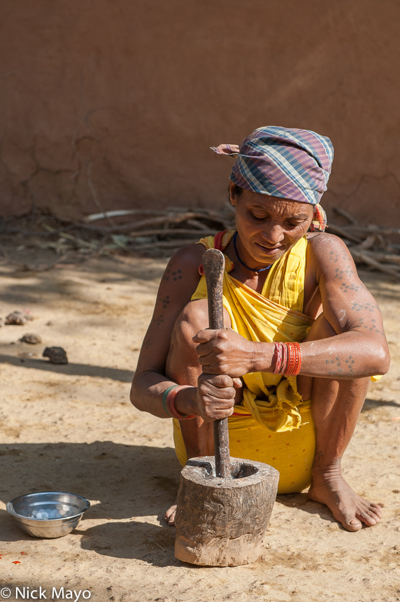 A traditionally tattooed Botra woman with mortar and pestle in the Gond village of Pajil.
