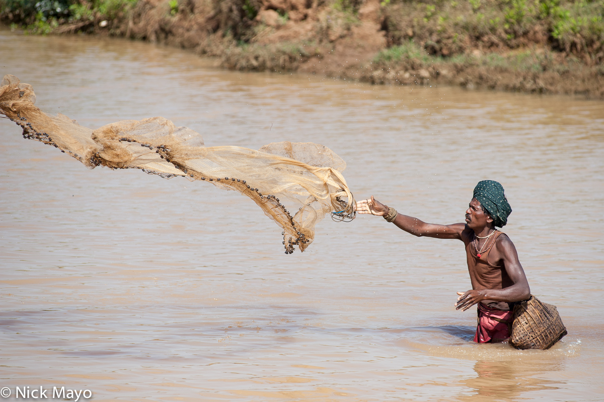 A turbanned fisherman, with basket and net, fishing near Jeypore.
