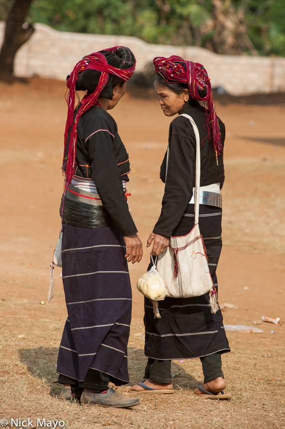 Two traditionally attired Paluang women holding a passing conversation at Loilom monastery on a shinbyu (novitiation) day.