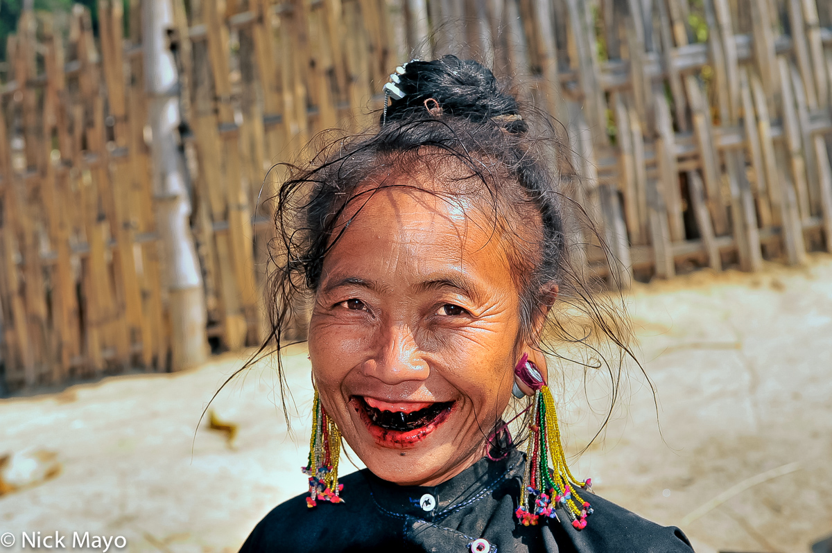 An Eng woman with long beaded earrings and betel stained teeth in Ban Nong village.