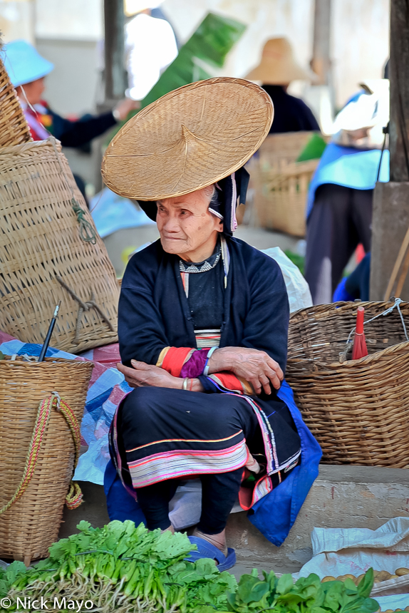 A Hua Yao Dai woman, wearing her traditional clothes and hat, selling vegetables at Mosha market surrounded by baskets.