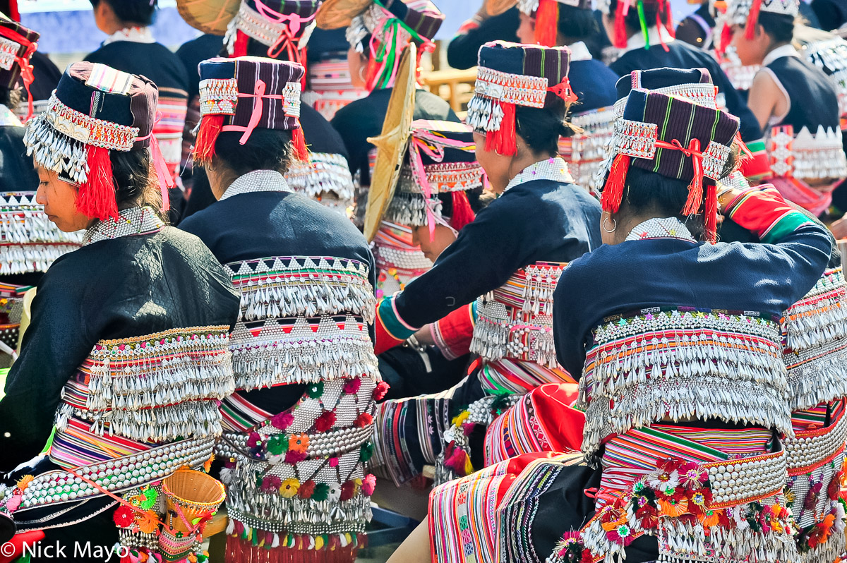 Hua Yao Dai women, wearing highly decorated backpieces and waist bands, waiting to dance at a festival in Mosha.