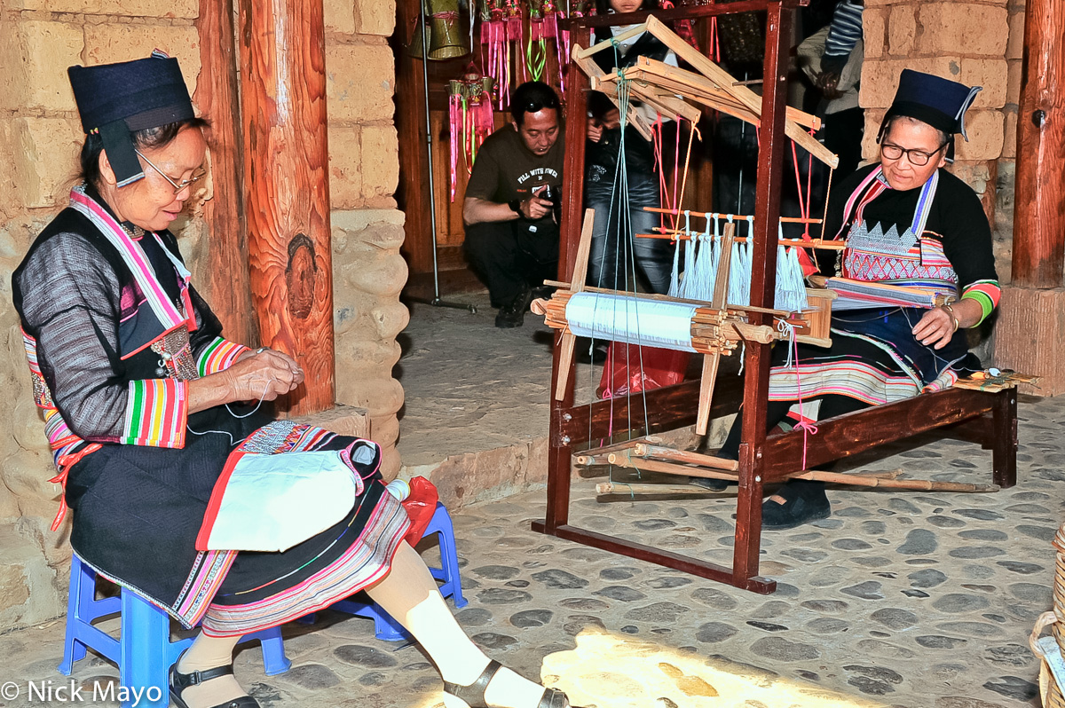 Two Hua Yao Dai women from Mosha, one weaving on a frame loom, the second stitching.