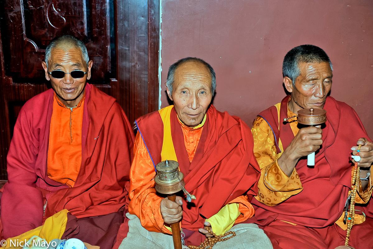 Three Tibetan monks at an assembly at the Larung Gar academy in Sertar.