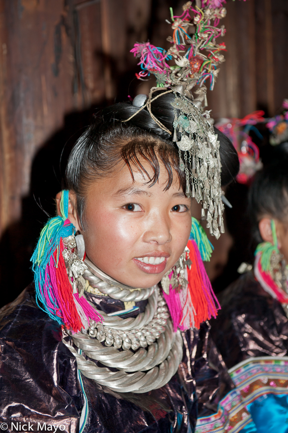 A Miao bridesmaid wearing a silver hair piece, heavy necklaces and multicoloured tasselled woollen earring at a wedding in the...