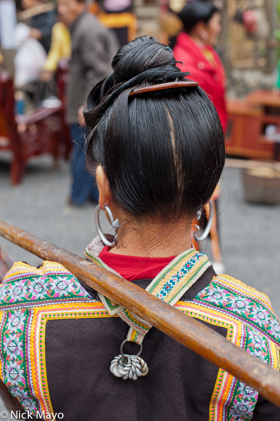 A Kazhai Miao woman, with a traditional hairstyle, wearing oversized earrings and a metal backpiece.
