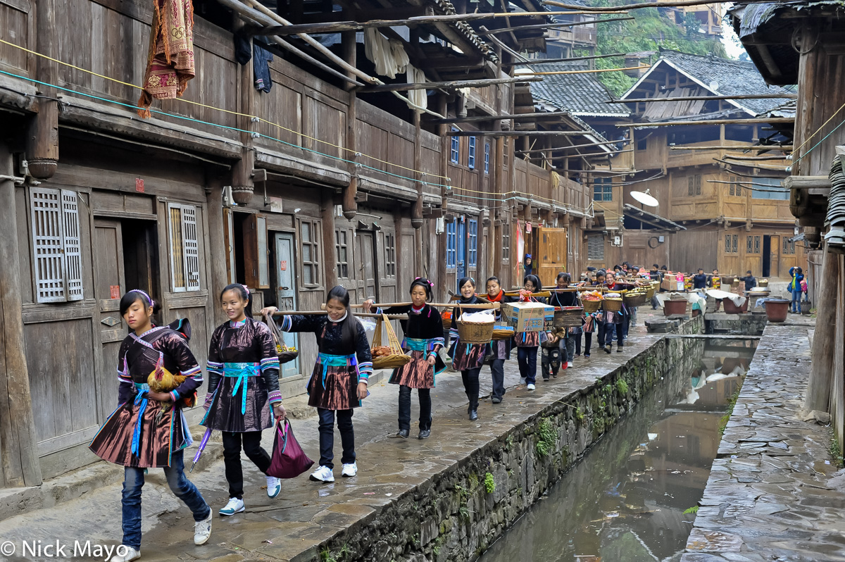 A wedding procession in the Dong village of Yintan on its way to the groom's house, headed by the bride symbolically holding...