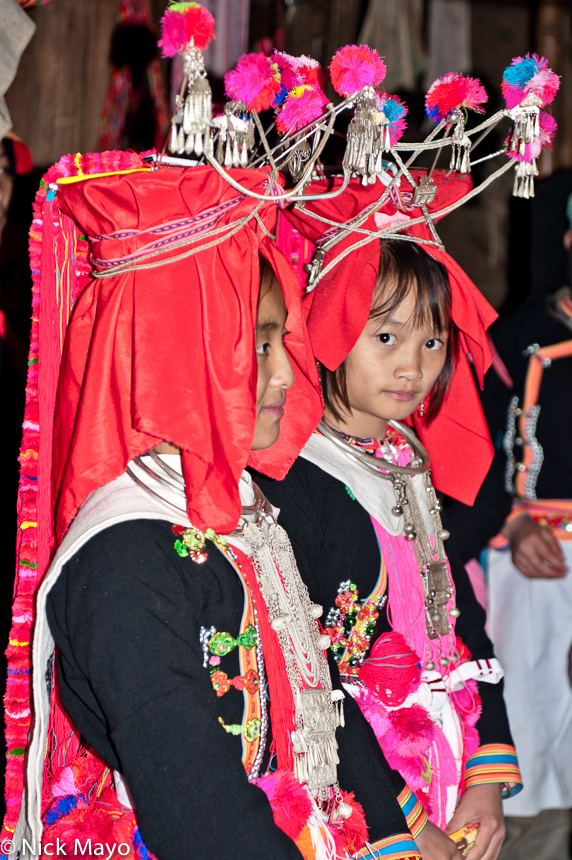 Bridesmaids, wearing traditional wedding hats and heavy necklaces & breastpieces, at a Yao wedding in Hui Yang Lao Zai.