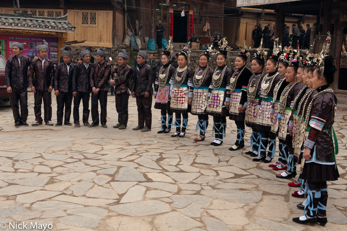 A group of Dong girls in festival dress singing antiphonally with a male group in Xiaohuang.