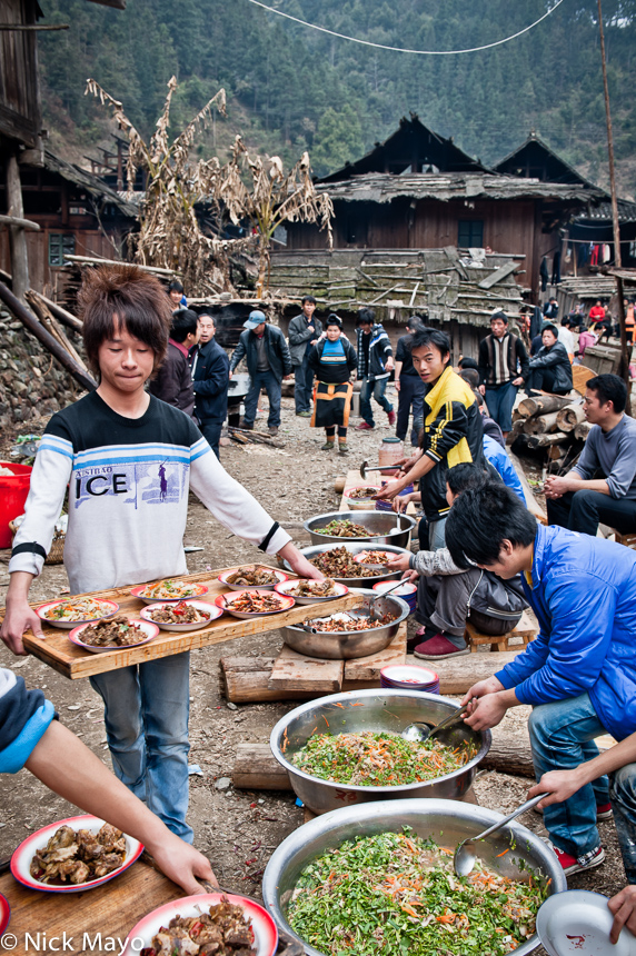 Miao youths serving vegetables at a wedding lunch in Cenzui.