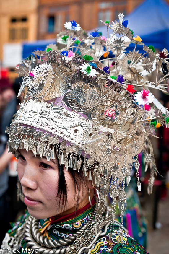 An unmarried girl wearing a crown headdress and silver necklace at a New Year festival in Yang Dong.
