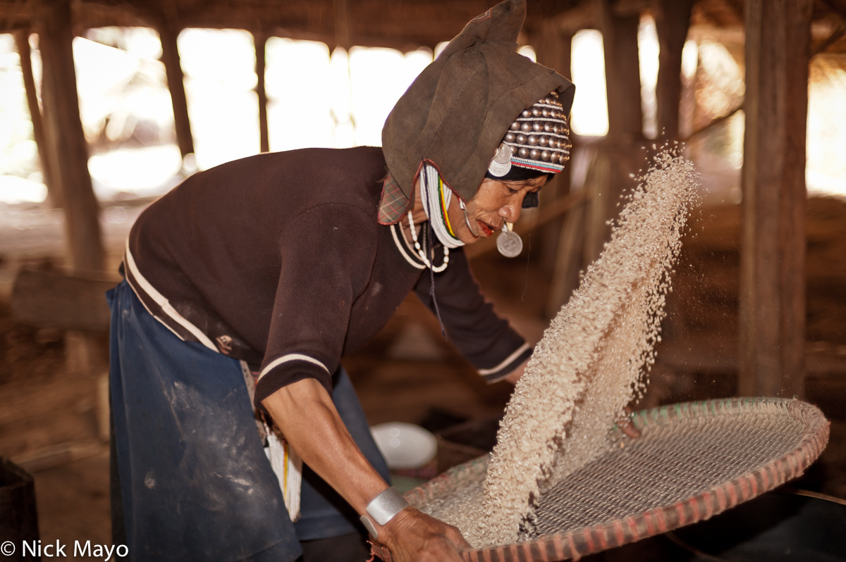 An Akha (Hani) woman wearing a traditional headdress, winnowing paddy rice in Ba Bei.