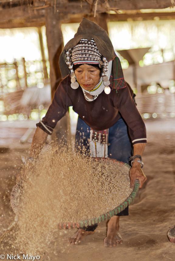 An Akha (Hani) woman, wearing a traditional headdress, winnowing paddy rice beneath her house in Ba Bei.