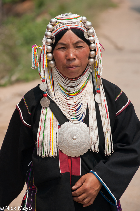 An Akha (Hani) woman from Hojin wearing a traditional breastpiece and headdress.