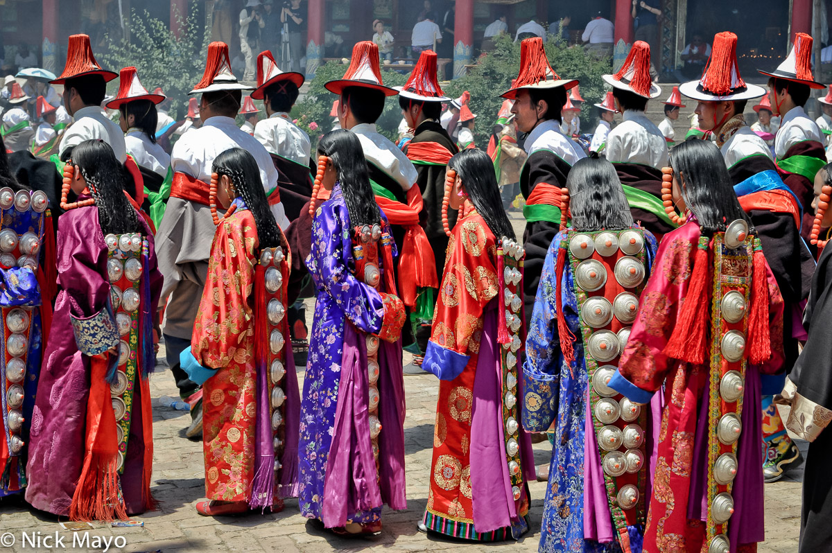 Tibetan men, wearing red tasselled hats, and girls, with heavy studded hair pieces hung from their braided hair, in a procession...