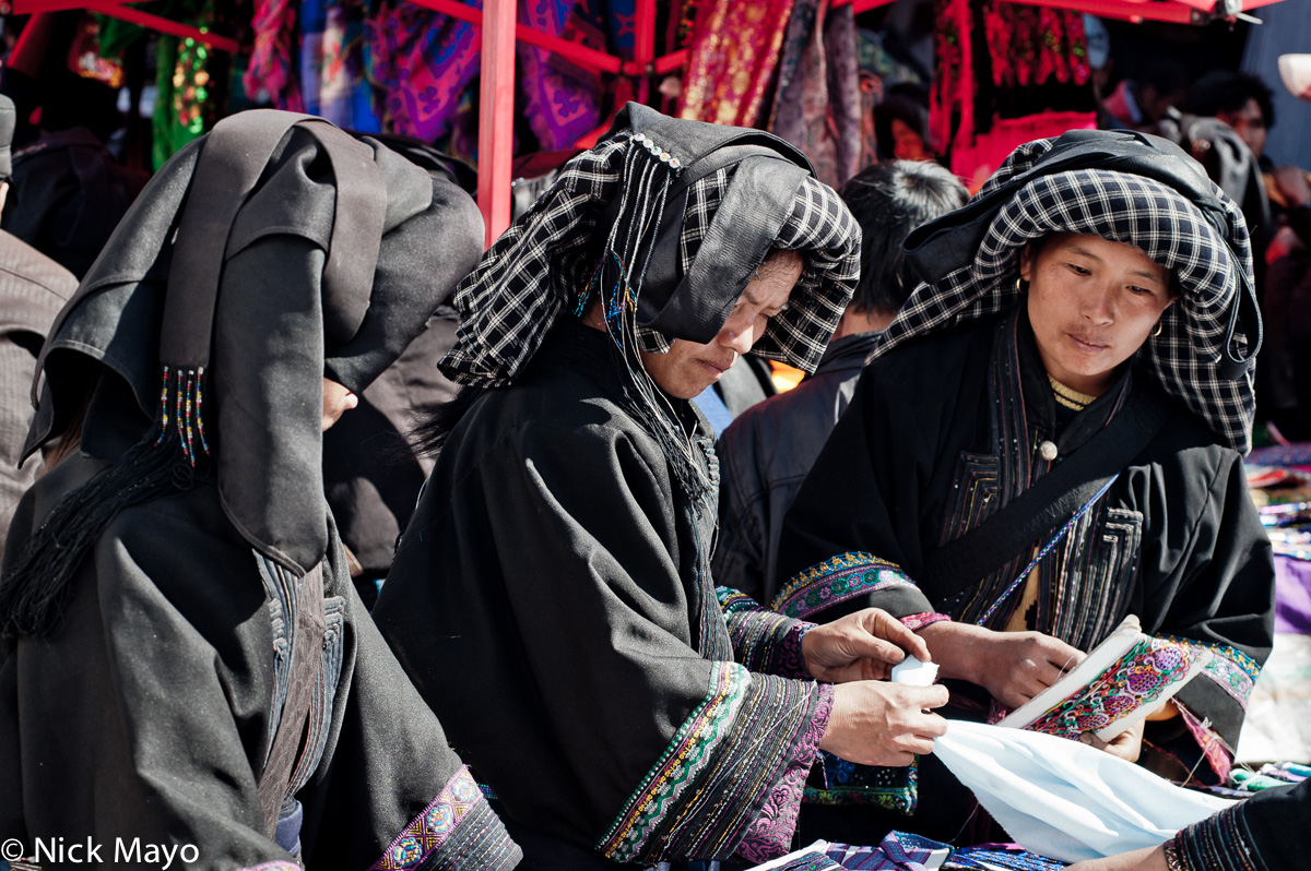 Three Limi Yi, wearing black and checkered turbans, shopping for cloth at Wumulonmg market.