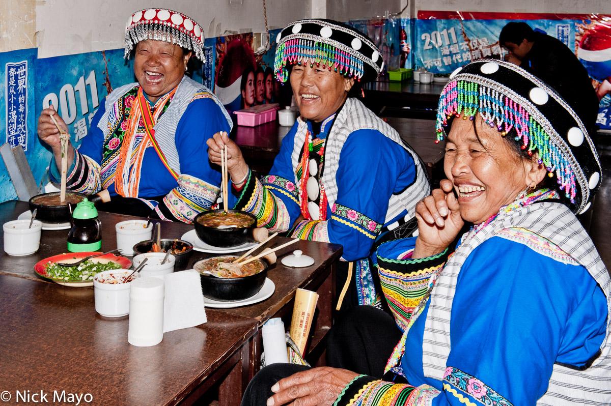 Three Lisu ladies eating lunch in a restaurant in Liu Ke.