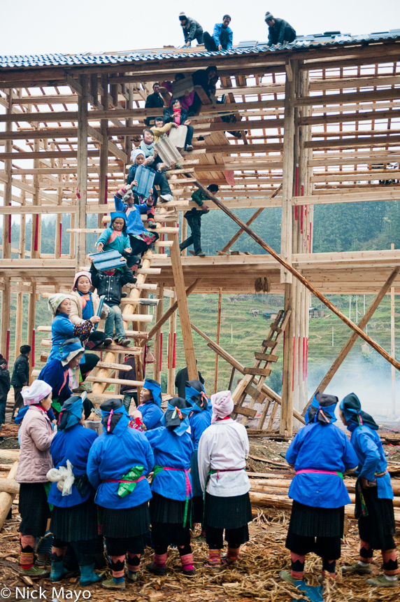 Traditionally dressed Miao women assisting in the construction of the roof of a house located near Bakai.