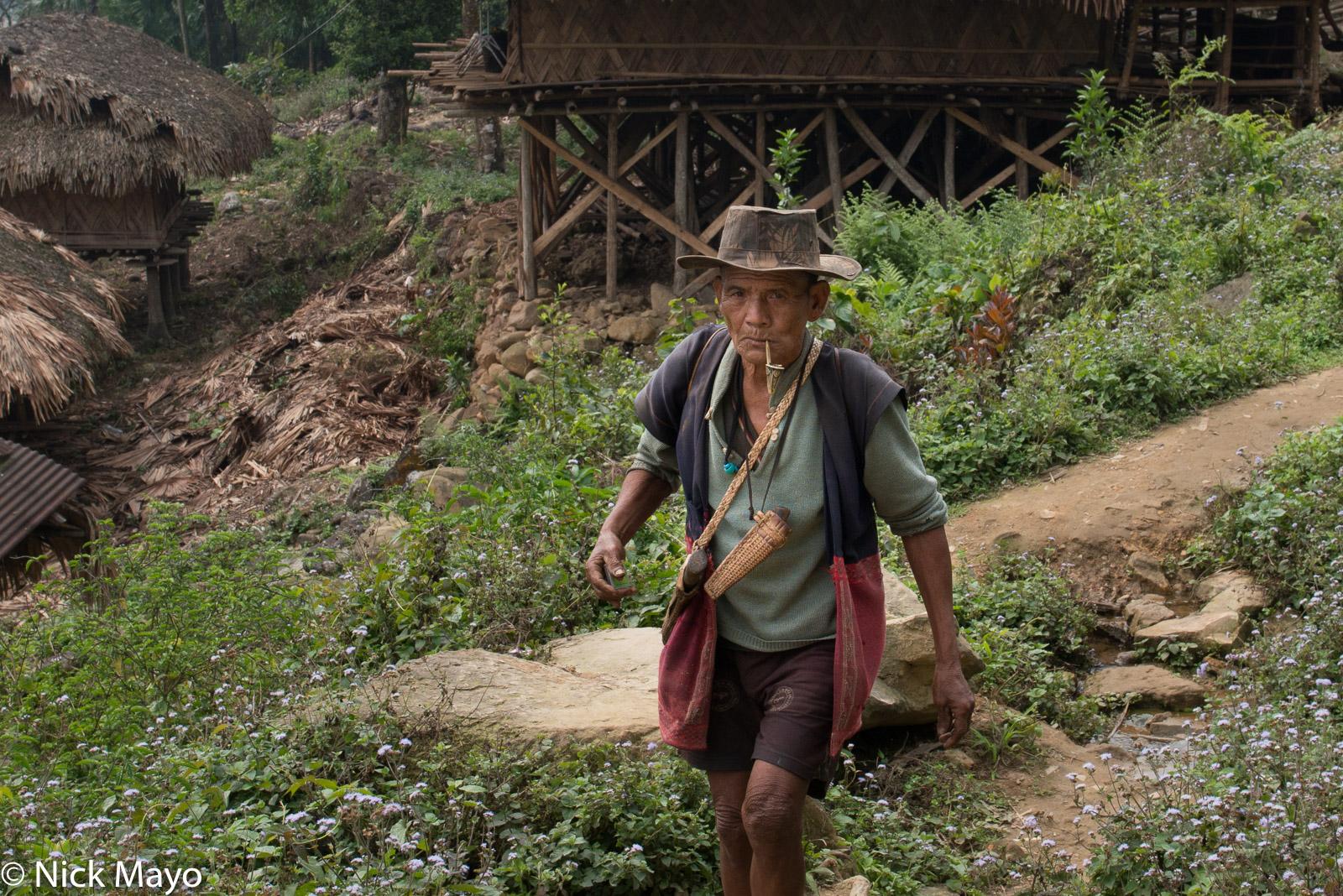 A pipe smoking Adi Minyong man in the village of Karang.