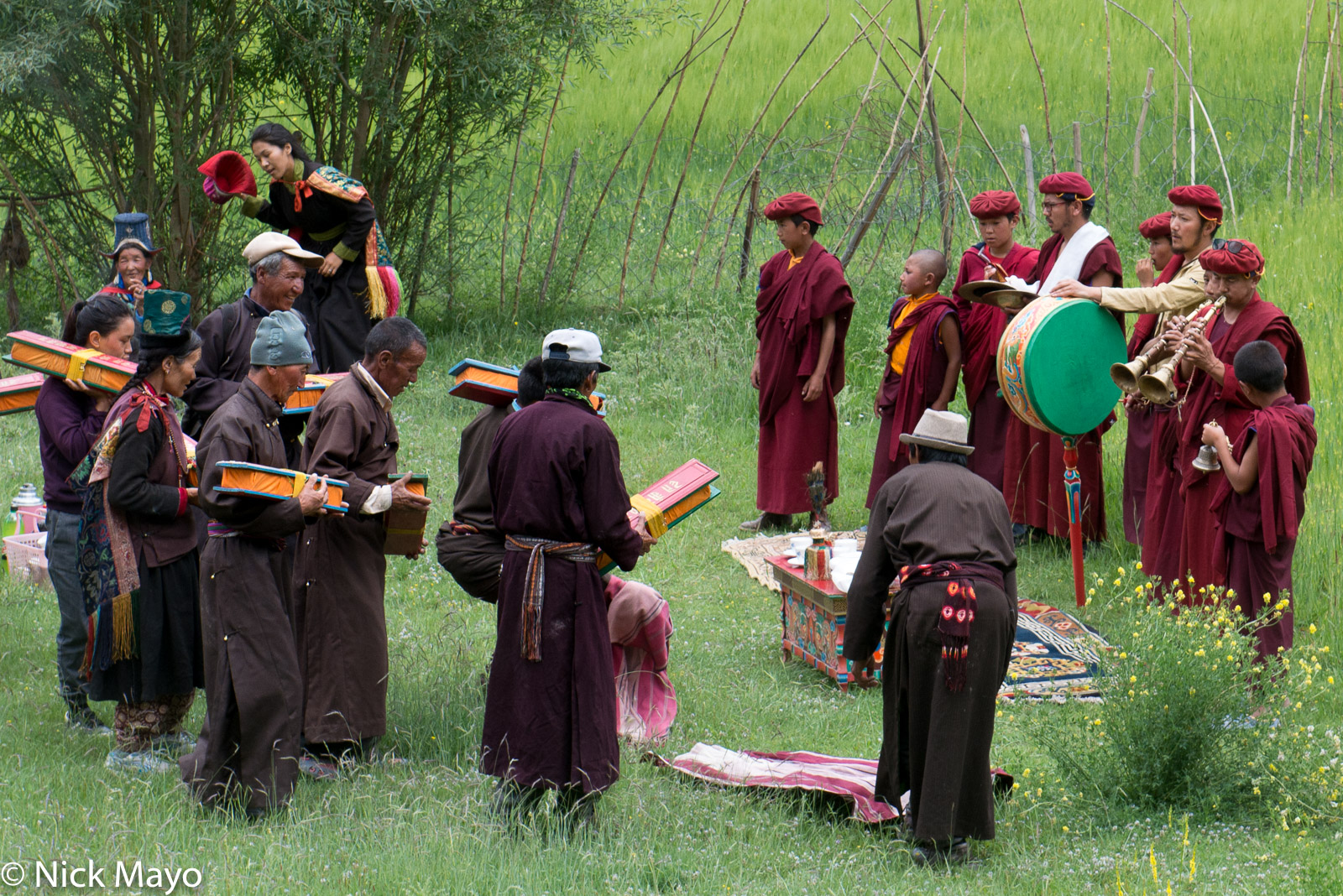 A religious ritual to bless the crops overseen by monks with a drum, cymbals, horns and a bell at Miru village.