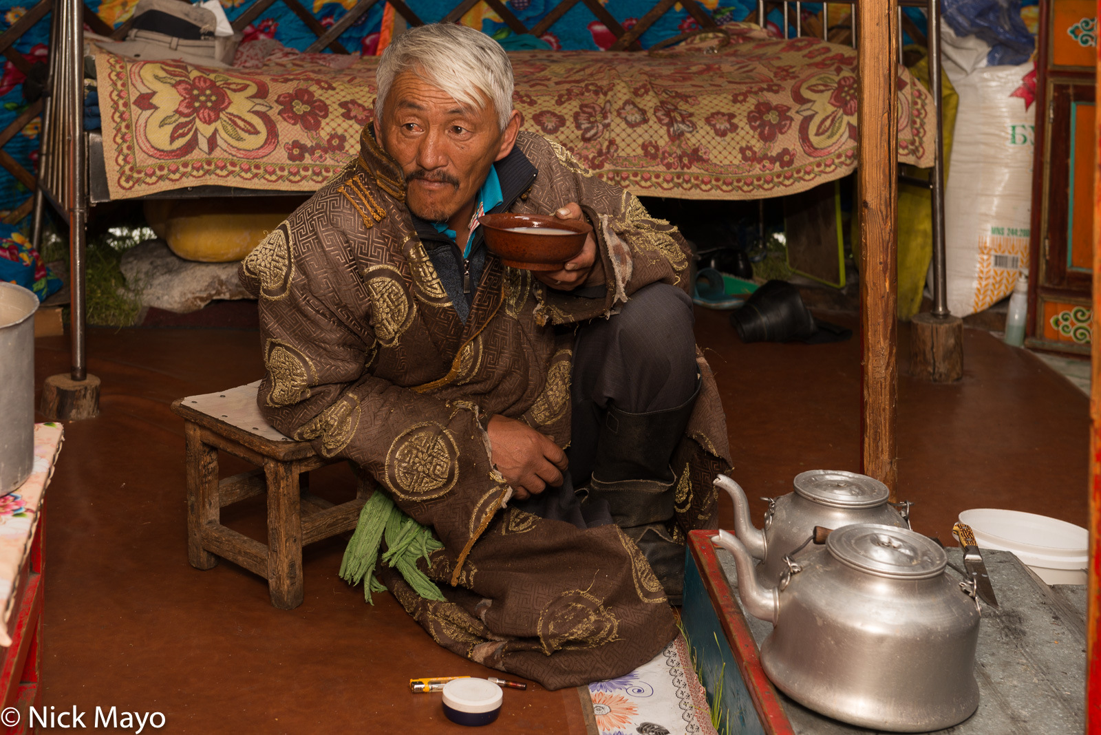 A Darkhad herder in his yurt on the Alag-Erdene steppe drinking tea while kettles boil on the stove.