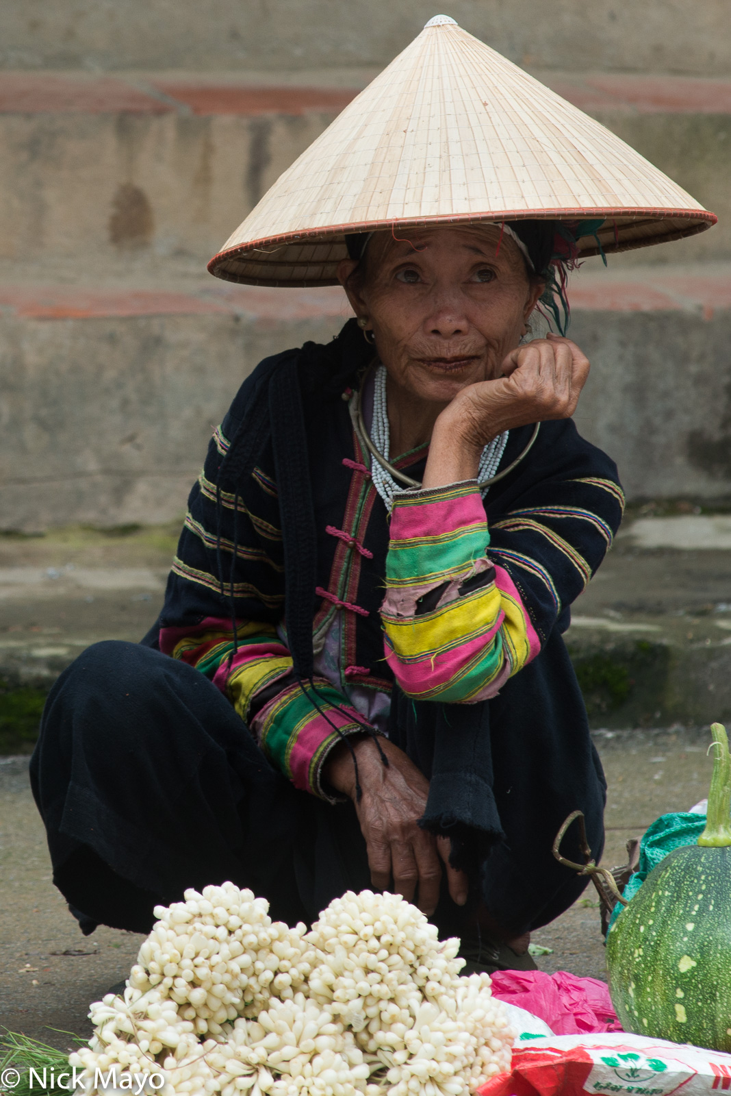 A Black Lolo woman selling vegetables at Bao Lac market.