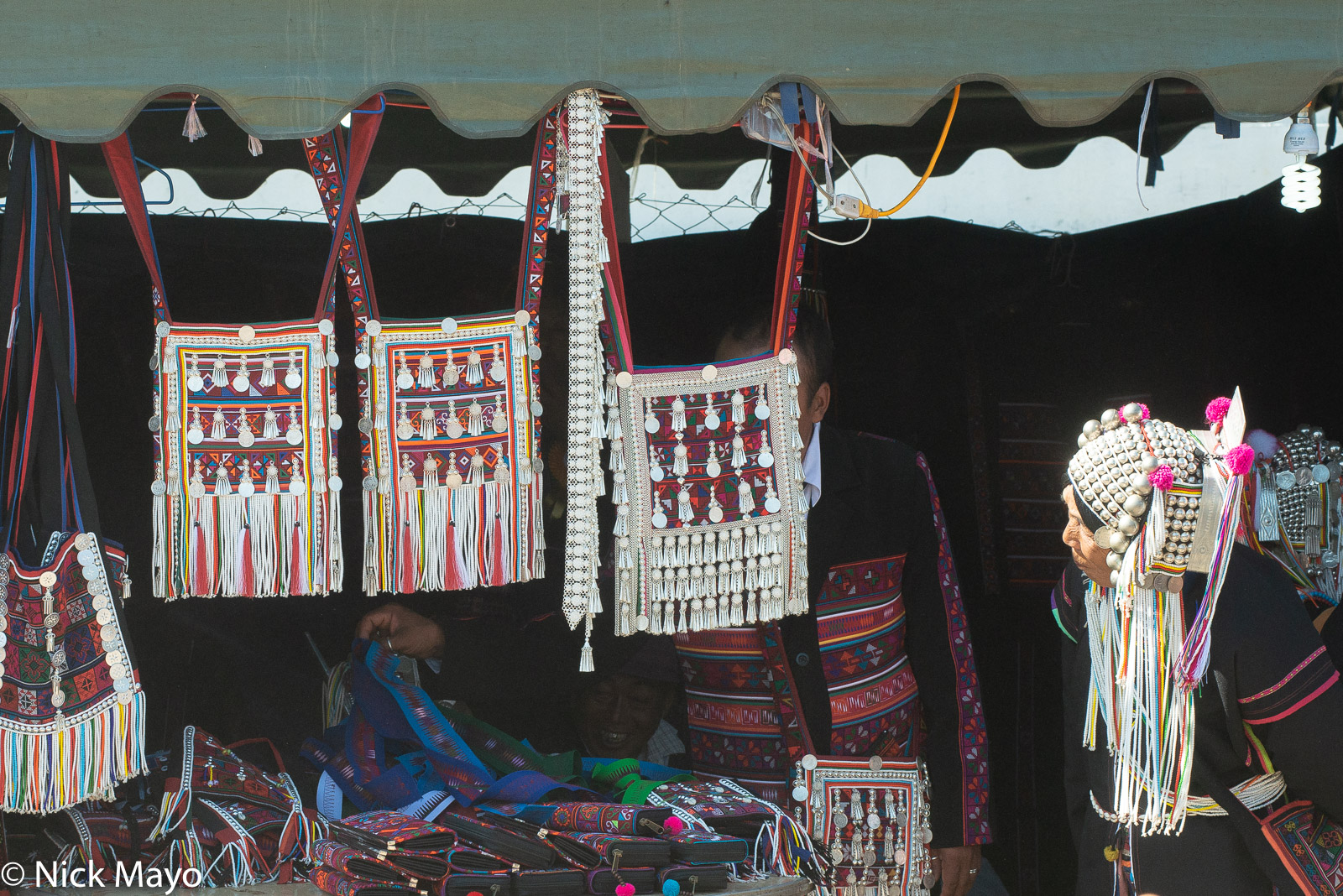 A woman studying bags on sale at an Akha (Hani) festival in Kengtung.