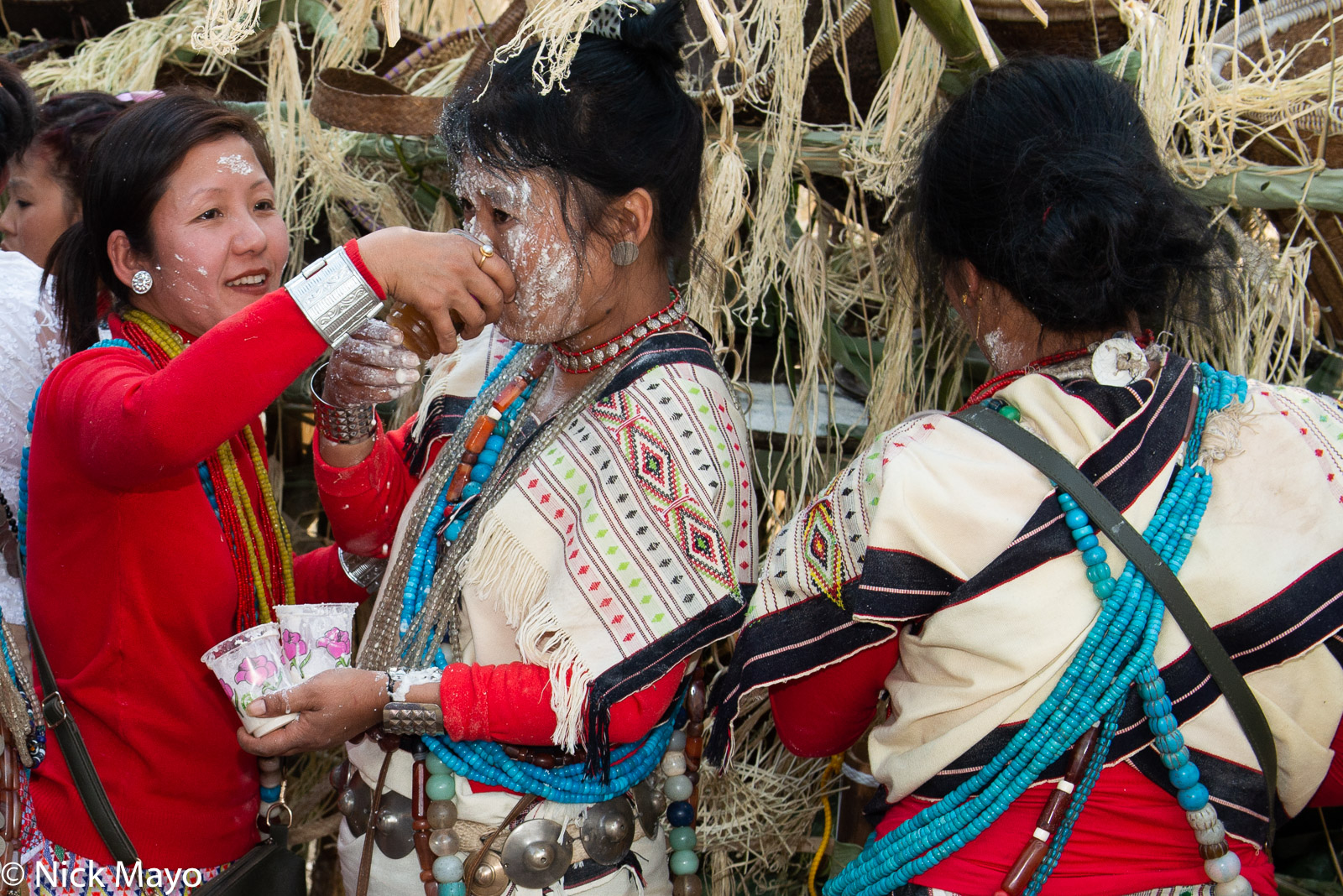 A Nyishi woman coated in rice powder drinking beer at the finale of the Tamen Boori Boot festival.