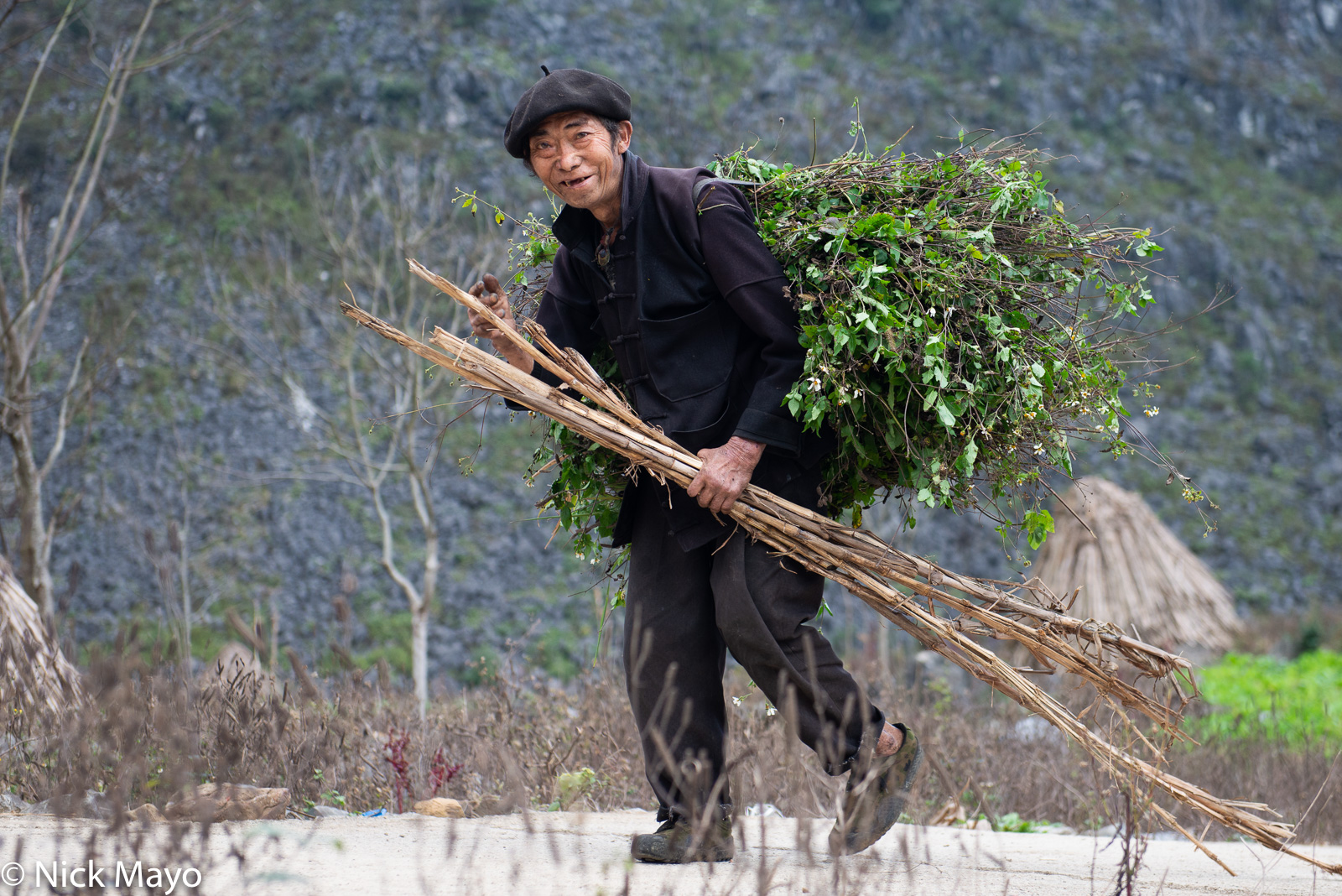 A farmer from the village of Cung Phin carrying home fodder.